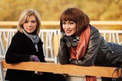 Deux jeunes femmes heureuses de mode sur un banc Photos stock