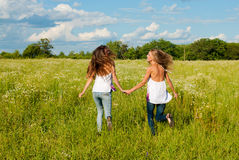 Deux jeunes femmes heureuses exécutant sur la zone verte Image stock