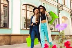 Deux jeunes femmes heureuses faisant des emplettes et portent des sacs Photos libres de droits