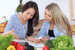 Deux jeunes femmes heureuses font des achats en ligne par la tablette et la carte de crédit Les amis vont faire cuire en Th Photographie stock