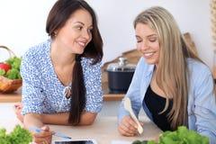 Deux jeunes femmes heureuses font des achats en ligne par la tablette et la carte de crédit Les amis vont faire cuire en Th Image libre de droits