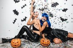 Deux jeunes femmes heureuses joyeuses dans des costumes en cuir de Halloween Images libres de droits