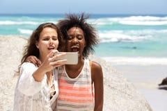 Deux jeunes femmes heureuses prenant le selfie à la plage Photographie stock
