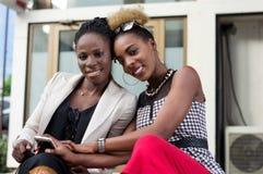 Deux jeunes femmes heureuses s'asseyant avec leurs têtes collées ensemble Image stock