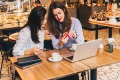 Deux jeunes femmes heureuses s'asseyent en café à la table devant l'ordinateur portable, utilisant le smartphone et rire Photo libre de droits