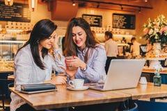 Deux jeunes femmes heureuses s'asseyent en café à la table devant l'ordinateur portable, utilisant le smartphone et rire Photographie stock libre de droits