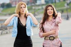 Deux jeunes femmes heureuses sur la rue de ville Photos stock