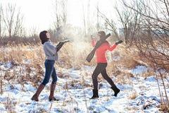 Deux jeunes femmes jetant la neige Image stock