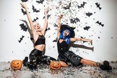 Deux jeunes femmes joyeuses dans la pose en cuir de costumes de Halloween Photographie stock libre de droits