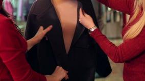 Deux jeunes femmes ? la mode choisissent des v?tements dans un magasin d'habillement ? la mode clips vidéos