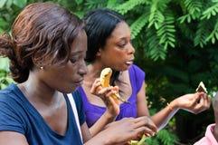 Deux jeunes femmes mangeant pendant leur campagne dans la relaxation images libres de droits
