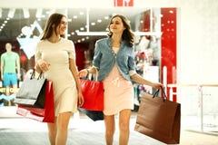 Deux jeunes femmes marchant avec des achats au magasin Photo libre de droits