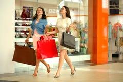 Deux jeunes femmes marchant avec des achats au magasin Photographie stock libre de droits