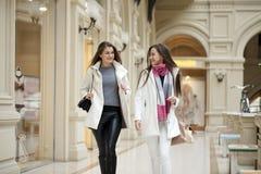Deux jeunes femmes marchant avec des achats au magasin Image libre de droits
