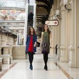 Deux jeunes femmes marchant avec des achats au magasin Photos stock