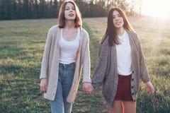 Deux jeunes femmes marchant sur la pelouse Images stock