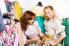 Deux jeunes femmes mesurant la taille de la jupe Photographie stock