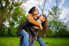 Deux jeunes femmes mignonnes dépensent gaiement le parc de temps au printemps Image libre de droits
