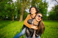 Deux jeunes femmes mignonnes dépensent gaiement le parc de temps au printemps Images stock
