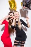 Deux jeunes femmes mignonnes de sourire avec des ballons célébrant et posant sur l'appareil-photo Image libre de droits