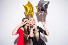 Deux jeunes femmes mignonnes de sourire avec des ballons célébrant et posant sur l'appareil-photo Photographie stock