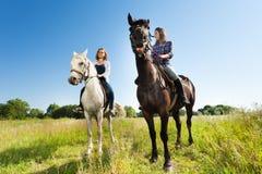 Deux jeunes femmes montant leurs beaux chevaux images stock