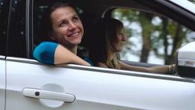 Deux jeunes femmes montent dans une voiture et ont l'amusement banque de vidéos