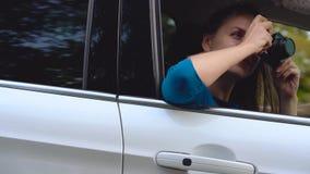 Deux jeunes femmes montent dans une voiture et ont l'amusement L'un d'entre eux prend une photo sur un appareil-photo de film Mou clips vidéos