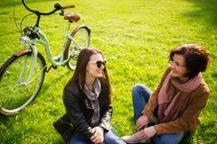 Deux jeunes femmes ont un repos sur une pelouse verte Photo stock