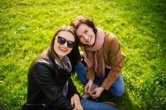 Deux jeunes femmes ont un repos sur une pelouse verte Photos stock
