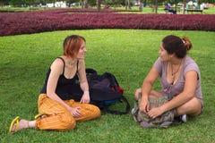 Deux jeunes femmes parlant en stationnement Images stock