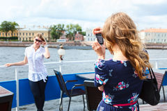 Deux jeunes femmes photographiant sur le bateau de croisière Photo stock
