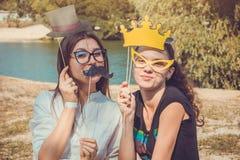 Deux jeunes femmes posant utilisant des appui verticaux de cabine de photo photographie stock