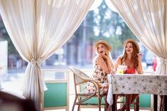 Deux jeunes femmes positives appréciant le smoothie frais en café Photos stock
