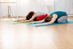 Deux jeunes femmes pratiquant l'asana de yoga sur le plancher dans le gymnase images libres de droits