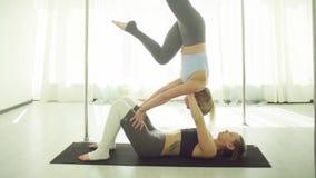 Deux jeunes femmes pratiquant le yoga acrobatique banque de vidéos