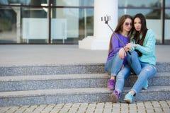 Deux jeunes femmes prenant des photos avec votre smartphone Images stock