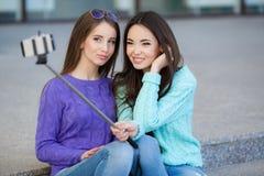 Deux jeunes femmes prenant des photos avec votre smartphone Photo stock