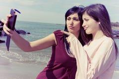 Deux jeunes femmes prenant le selfie devant la plage faisant le vintage drôle de visages regarder Images libres de droits