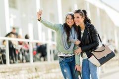 Deux jeunes femmes prenant un autoportrait de lui-même Image stock