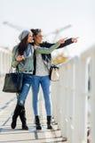Deux jeunes femmes regardant au-dessus d'une barrière de dock et se dirigeant dans un grand Image libre de droits
