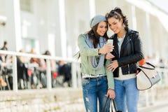 Deux jeunes femmes regardant le téléphone tout en étant près de l'eatch Photo stock