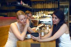 Deux jeunes femmes regardant un comprimé numérique Images stock