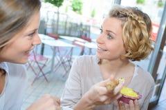 Deux jeunes femmes riant et mangeant en café Images libres de droits
