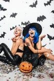Deux jeunes femmes riantes dans des costumes en cuir de Halloween Image stock
