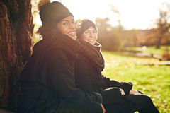Deux jeunes femmes s'asseyant en parc automnal et souriant à l'appareil-photo Photo libre de droits