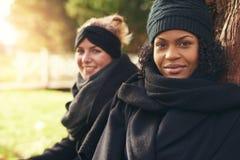 Deux jeunes femmes s'asseyant en parc automnal et souriant à l'appareil-photo Images libres de droits