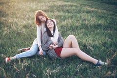 Deux jeunes femmes s'asseyant sur l'herbe Images stock