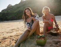 Deux jeunes femmes s'asseyant sur la plage et le sourire Photos stock