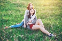 Deux jeunes femmes s'asseyant sur le champ Photographie stock libre de droits